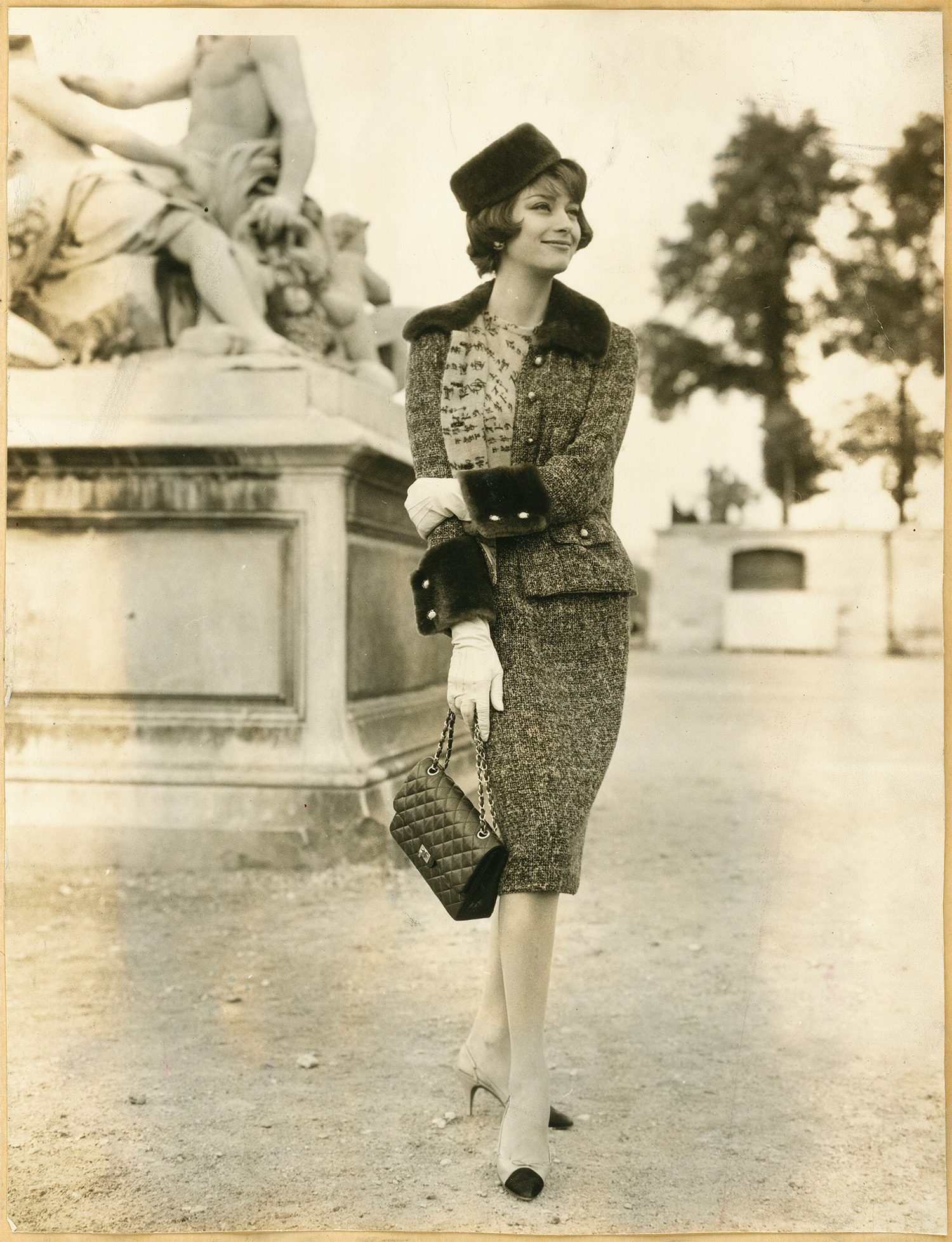 Marie-Hélène Arnaud wearing a tweed suit from the Fall-Winter 1959-60 Haute Couture collection and the 2.55 bag © CHANEL All rights reserved
