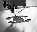 5. Lavorazione e creazione della 2.55 handbag by CHANEL© - La doppia C viene cucita sulla parte interna della pelle